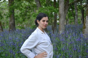 Personal Chef and Holistic Nutritionist Khalilah Alwani standing in front of a camas forest in Victoria on Lekwungen and WSANEC lands, turned to side, hand on hip